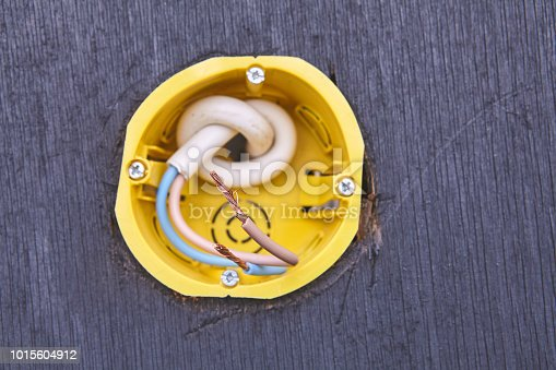 1015605026 istock photo Yellow outlet box for wall socket, close-up. 1015604912