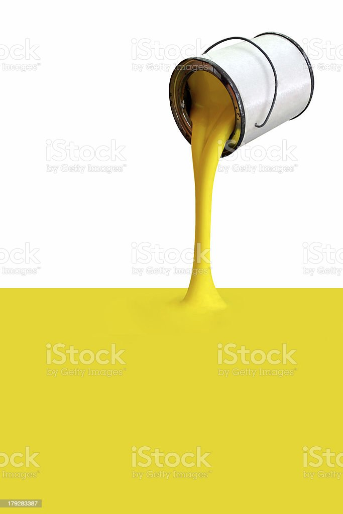 Yellow paint pours from silver can stock photo