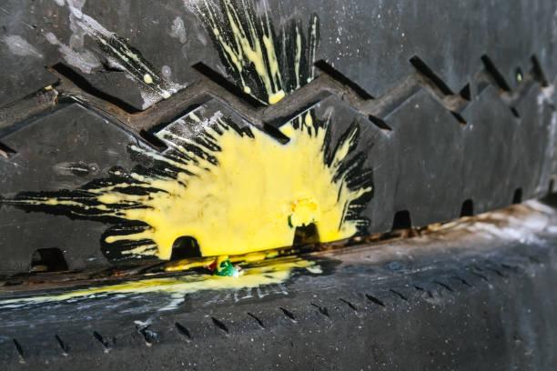 Éclaboussure jaune de peinture d'un paintball écrasé sur un vieux pneu de voiture avec un modèle de bande de roulement en zigzag. Mise au point sélective - Photo