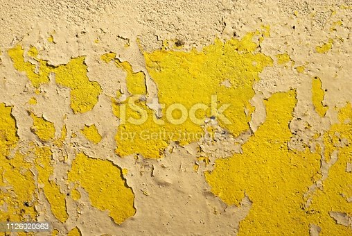 Yellow painted concrete wall textured background with peeling paint