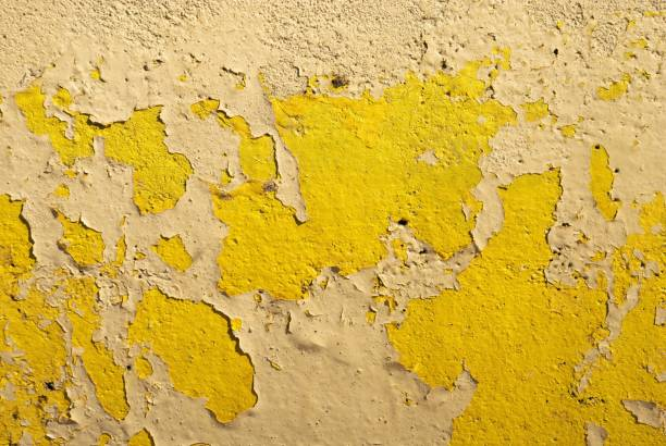 Yellow painted concrete wall textured background with peeling paint stock photo