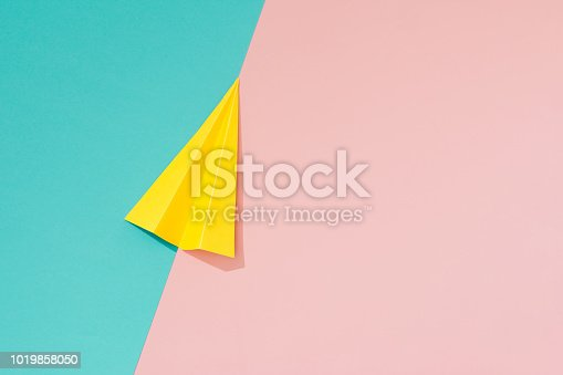 istock Yellow paper airplane on pastel pink and blue background. 1019858050