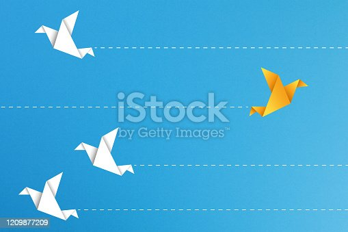 1088508096 istock photo Yellow paper bird goes in a different direction from the white paper birds on blue background, different business concept 1209877209