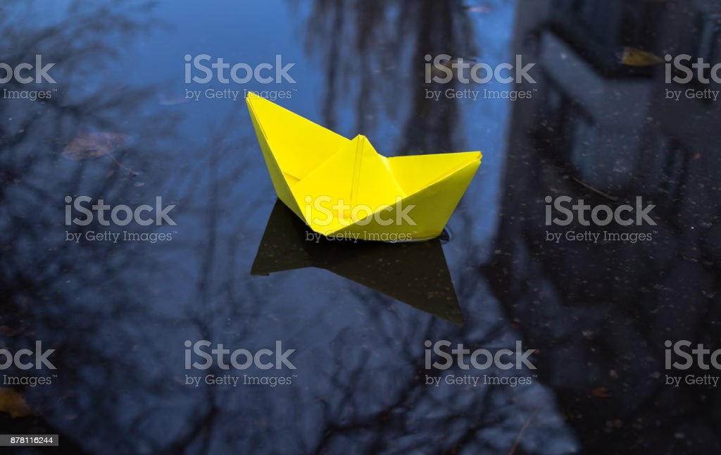 bright yellow paper boat on a background of gloomy autumn urban...