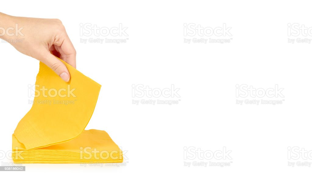 Yellow paper napkin for food in hand isolated on white background. Kitchen serving object. copy space, template stock photo