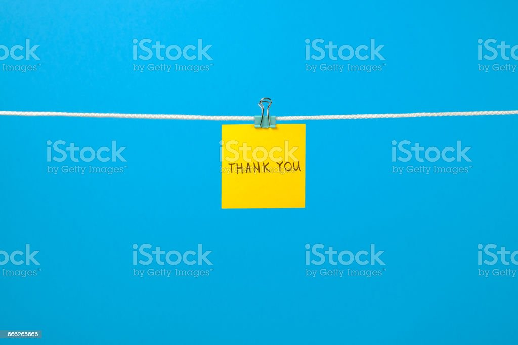 Yellow paper note on clothesline with text Thank You over colorful background stock photo