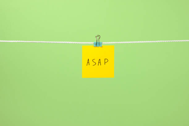 Yellow paper note on the string with text ASAP over colorful background Yellow paper note on the string with text ASAP over colorful background ASAP stock pictures, royalty-free photos & images