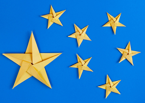 Yellow Paper Origami Stars on Blue Background
