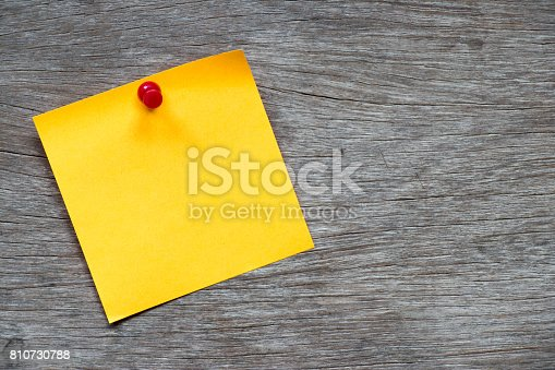 istock Yellow paper pin on brown wood background for memo, notice or to do list 810730788