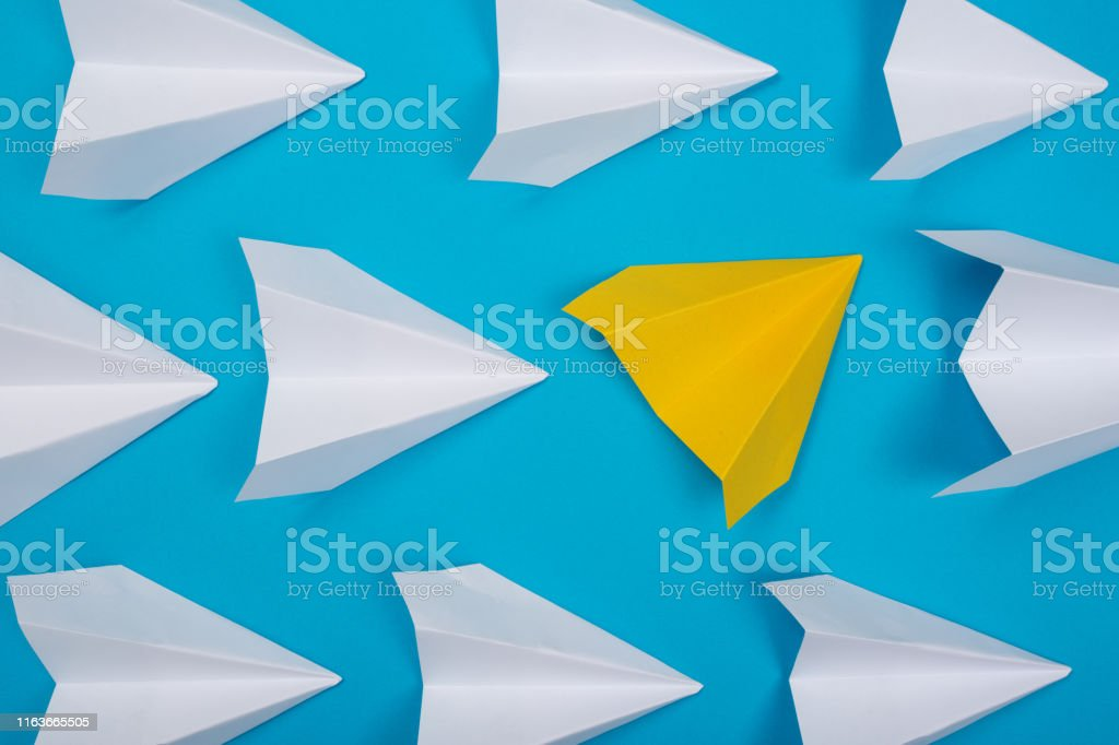 Yellow paper plane are different from others on blue background....