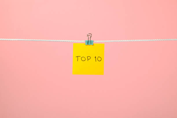 Yellow paper sheet on the string with text Top 10 over colorful background stock photo