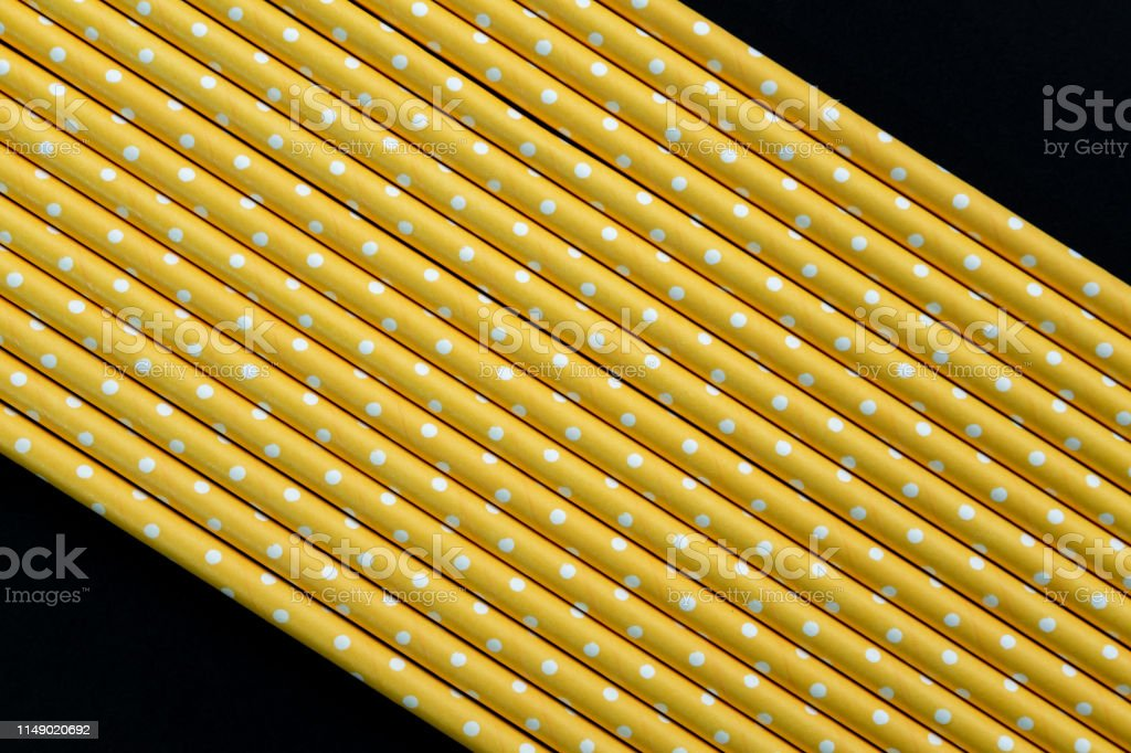 Yellow paper straws isolated on black background