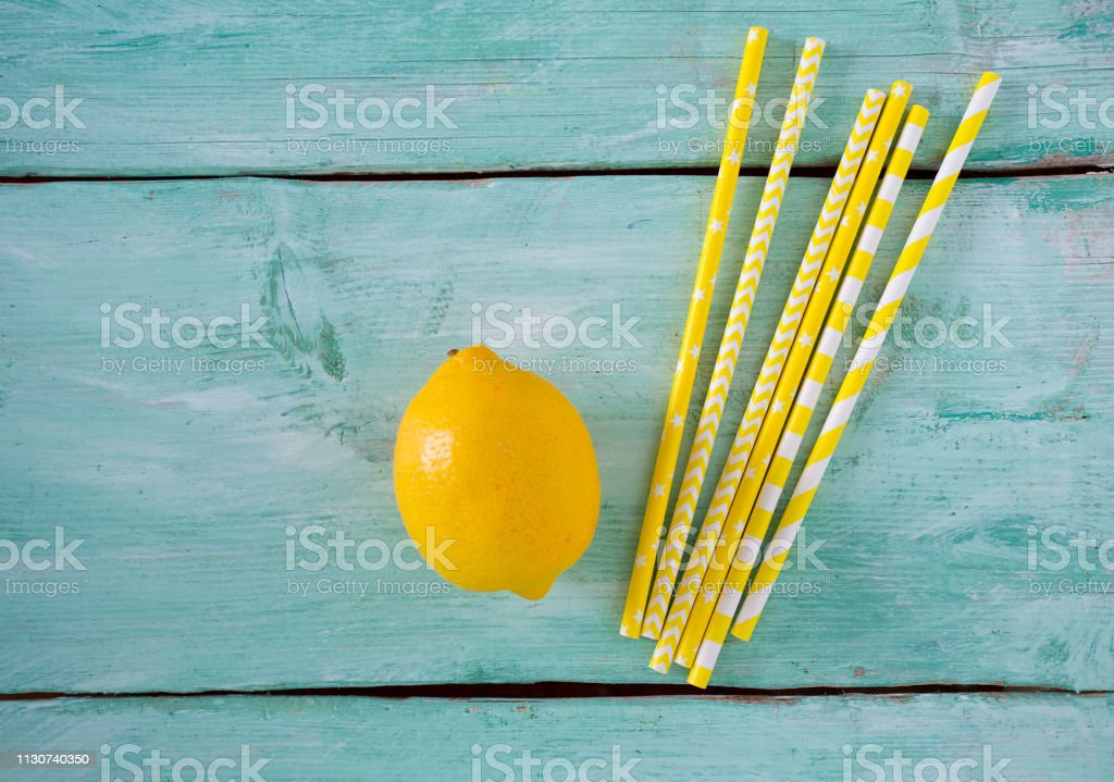 yellow paper straws on turquoise wooden background with lemon