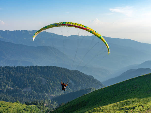 Yellow paraglider in blue clear sky over the Green Mountain Paraglider in blue clear sky over the Green Mountain paragliding stock pictures, royalty-free photos & images
