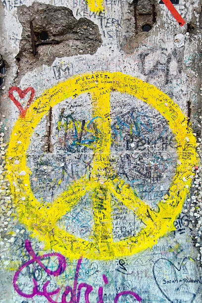 yellow peace sign on berlin wall - symbols of peace stock pictures, royalty-free photos & images