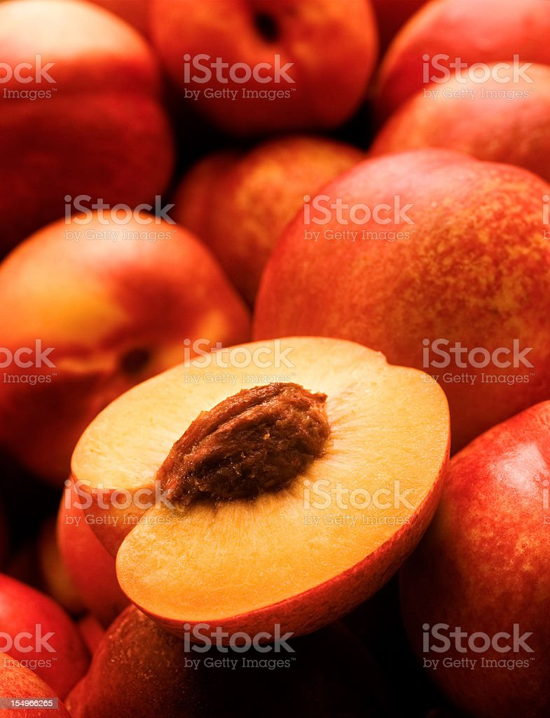 A yellow peach opened on top of other peaches royalty-free stock photo