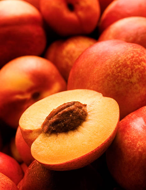 A yellow peach opened on top of other peaches stock photo