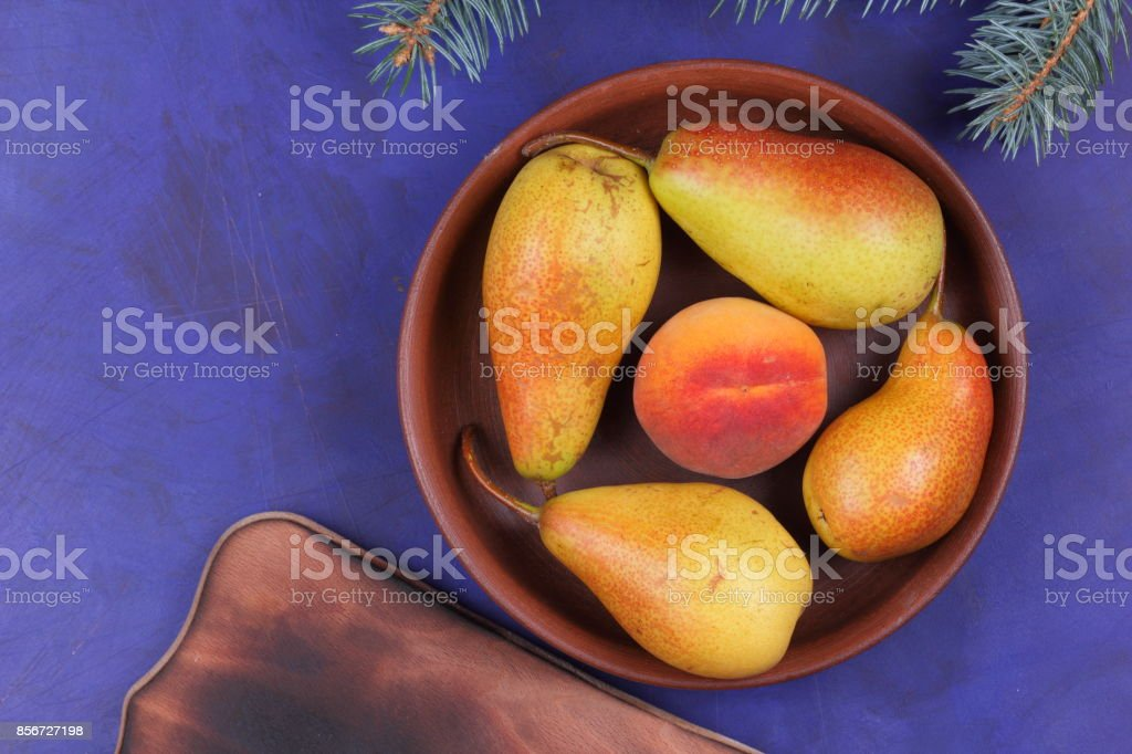 Yellow pears and peach on a clay plate with Christmas tree branches for Christmas dinner stock photo