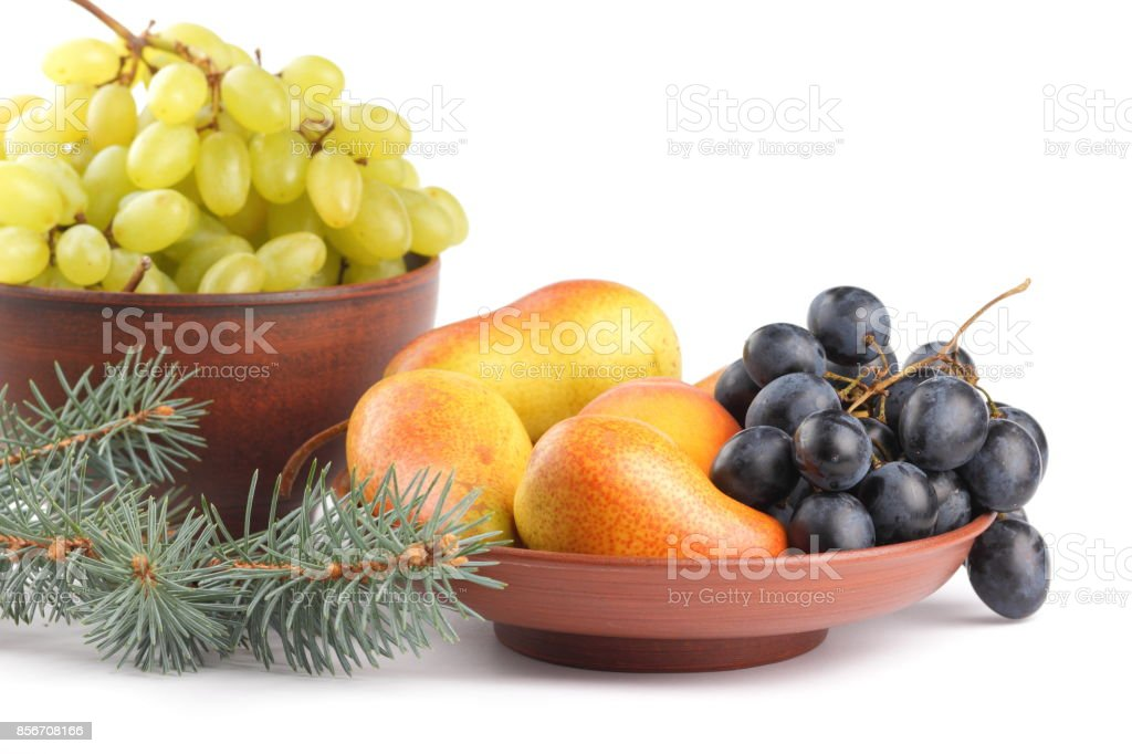 Yellow pears, green and blue grapes in a clay plate with Christmas tree branches on a Christmas dinner on a white background stock photo
