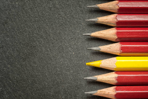Yellow pencil standing out from crowd of plenty identical black fellows on black  table. Leadership, uniqueness, independence, initiative, strategy, dissent, think different, business success concept. stock photo
