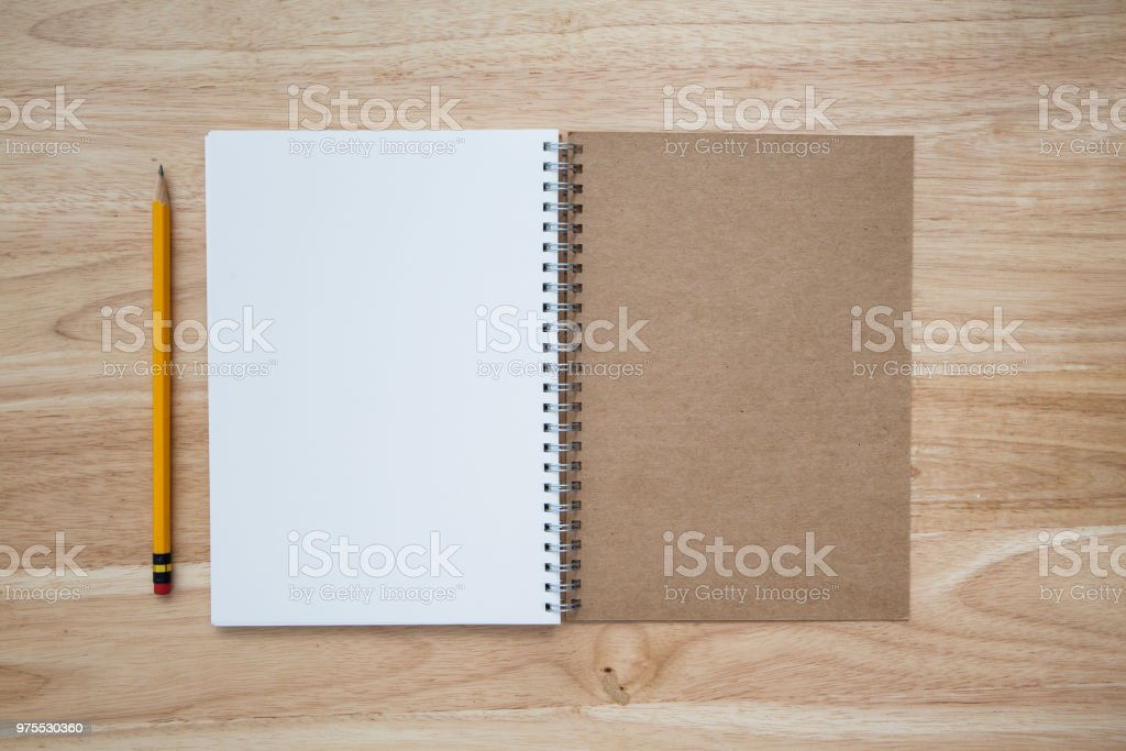 yellow pencil with note book on wood table stock photo