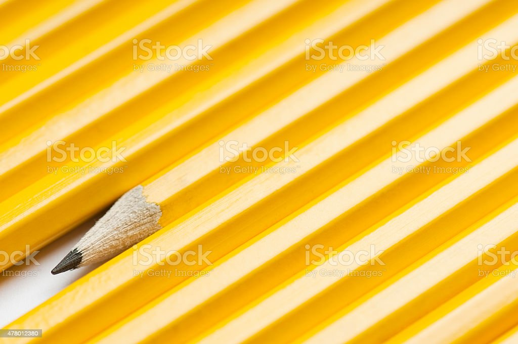 Yellow pencils lined up showing one sharp pencil nib stock photo