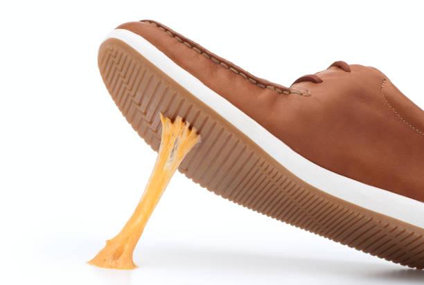 Yellow piece of gum stuck on bottom of brown shoe stock photo