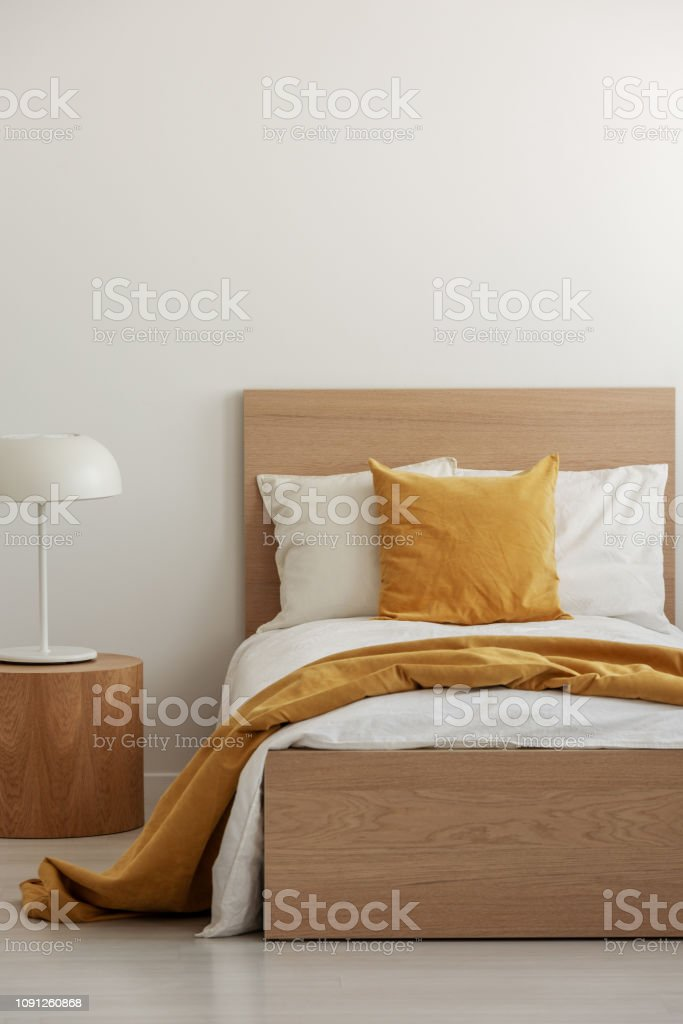 Yellow pillow and blanket on white bedding in simple hotel room with...
