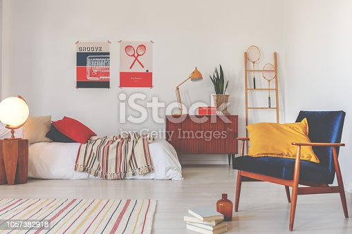 Yellow pillow on blue vintage armchair in stylish oldschool bedroom for teenager