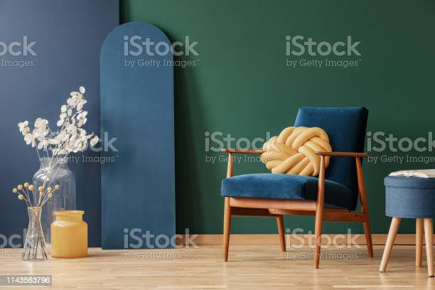 Yellow pillow on wooden armchair in blue and green flat interior with picture id1143563796?b=1&k=6&m=1143563796&s=612x612&h=tl0ceyvbrcpbedoduj67efrl6nktx4a2s6shboqmjvy=