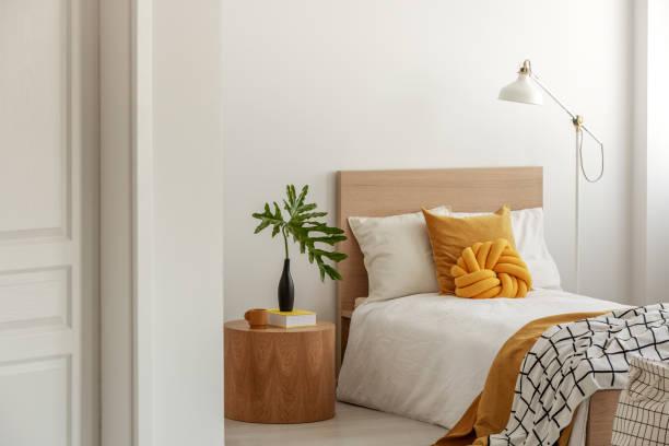 Gelbe Kissen und Decke auf weißem Holzeinzelbett – Foto