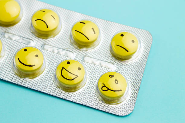 Yellow pills andfunny faces in a blister on a blue background. stock photo