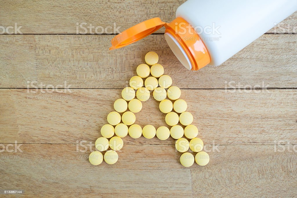 Yellow pills forming shape to A alphabet on wood background stock photo