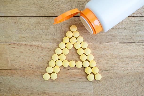 comprimidos amarillos formando la forma de una letra del alfabeto en fondo de madera - vitamina a fotografías e imágenes de stock