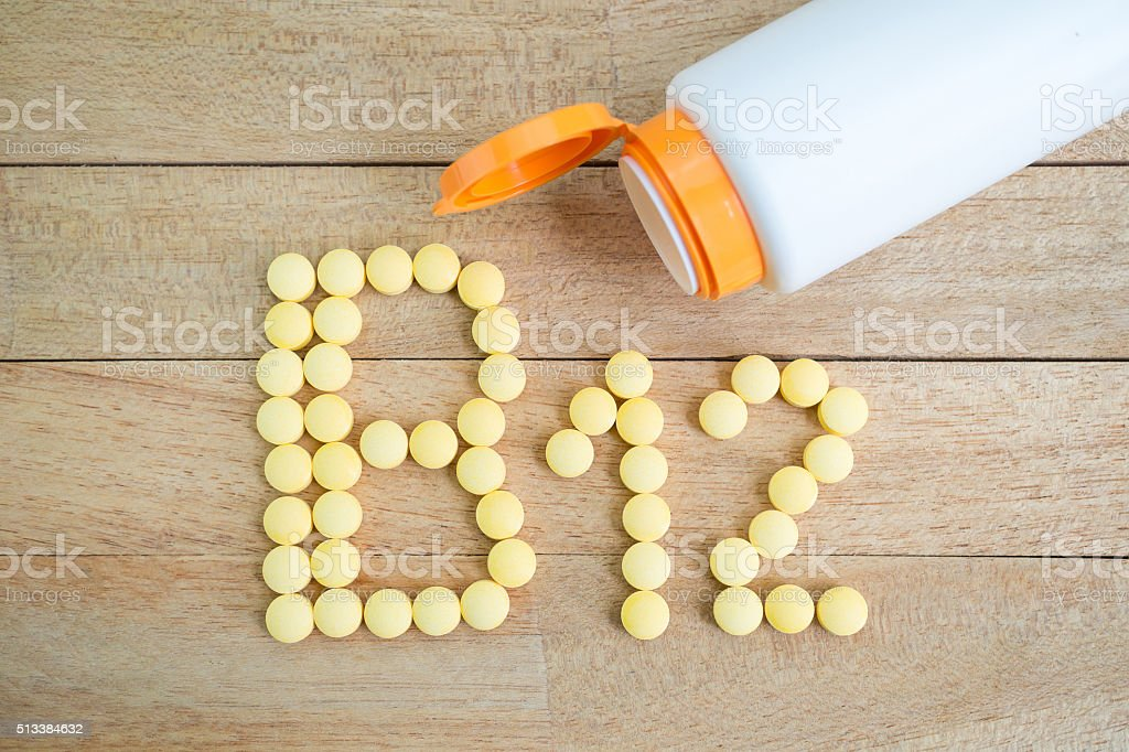 Yellow pills forming shape to B12 alphabet on wood background stock photo