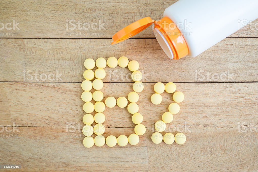 Yellow pills forming shape to B2 alphabet on wood background stock photo