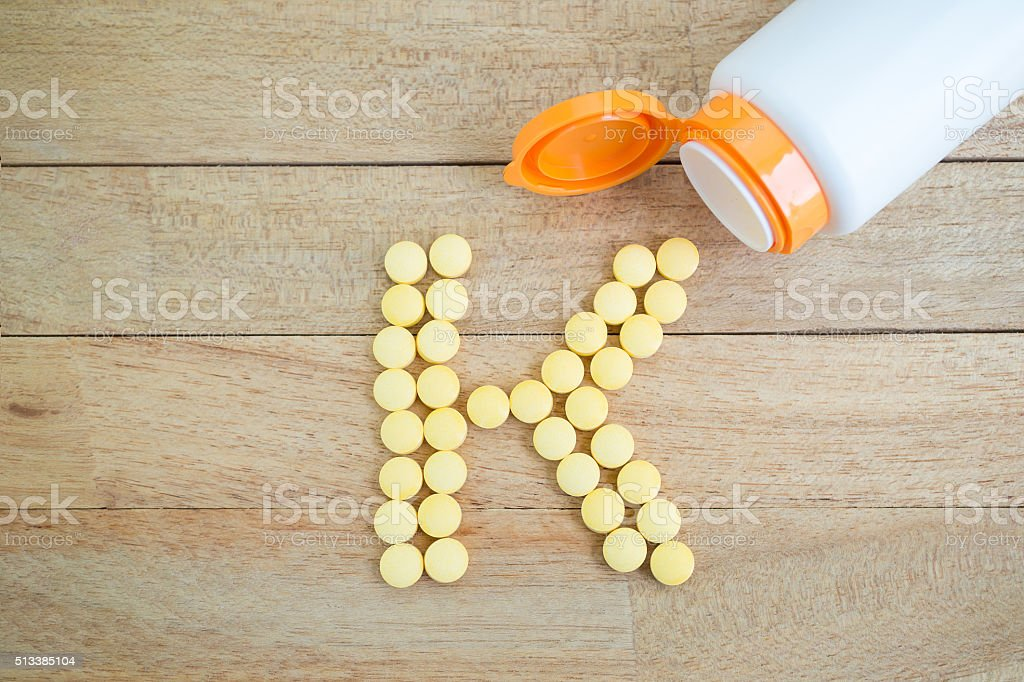 Yellow pills forming shape to K alphabet on wood background stock photo