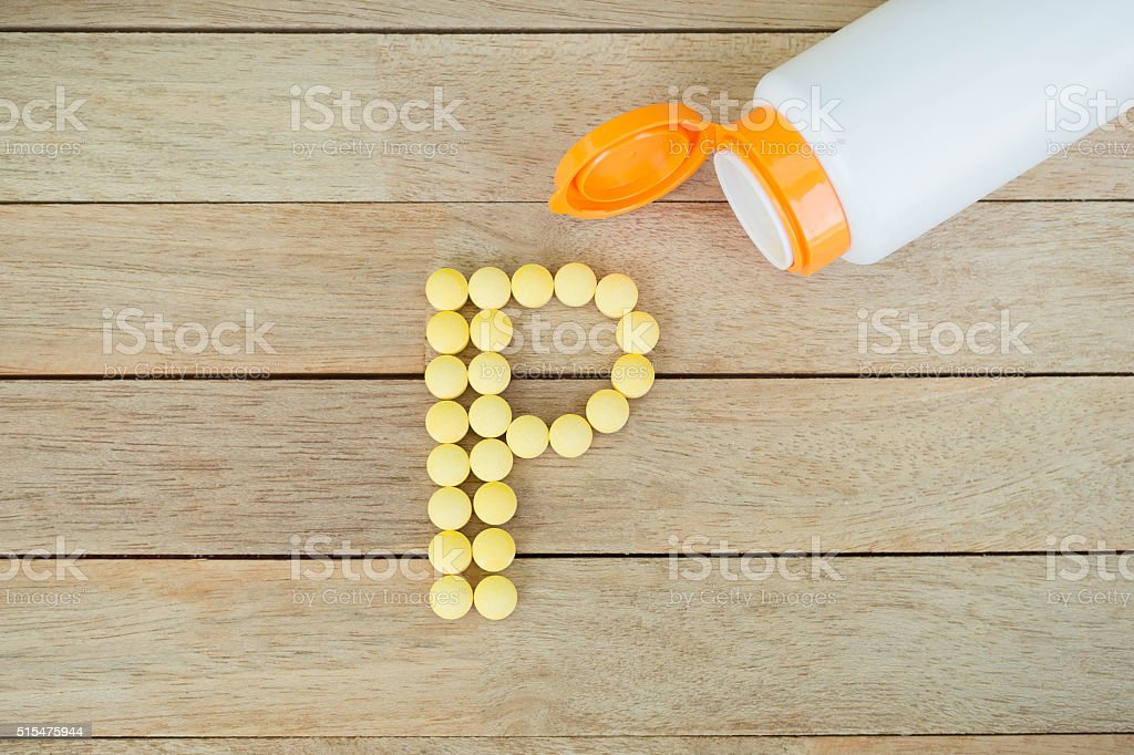 Yellow pills forming shape to P alphabet on wood background stock photo