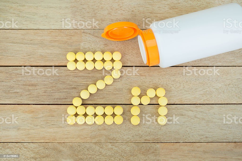 Yellow pills forming shape to Zn alphabet on wood background stock photo