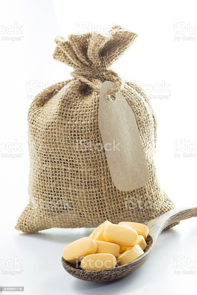 Yellow Pills In Empty Burlap Sack And On Spoon Stock Photo