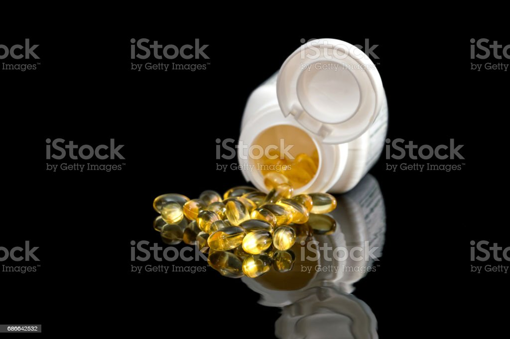 Yellow pills with pill bottle on the black reflective background. royalty-free stock photo