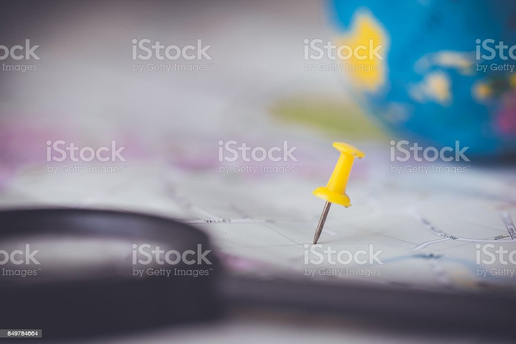 Yellow pin on the map with magnifying glass stock photo