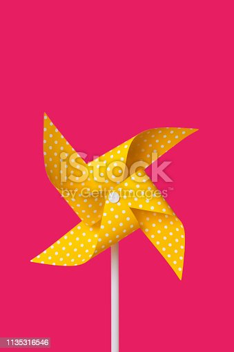 closeup of a yellow pinwheel patterned with white dots against a bright fuchsia background with a blank space on top