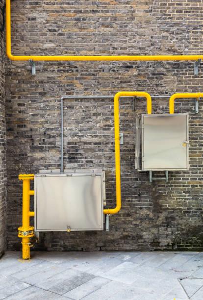 Tuberías amarillas y paredes de ladrillo antiguo - foto de stock