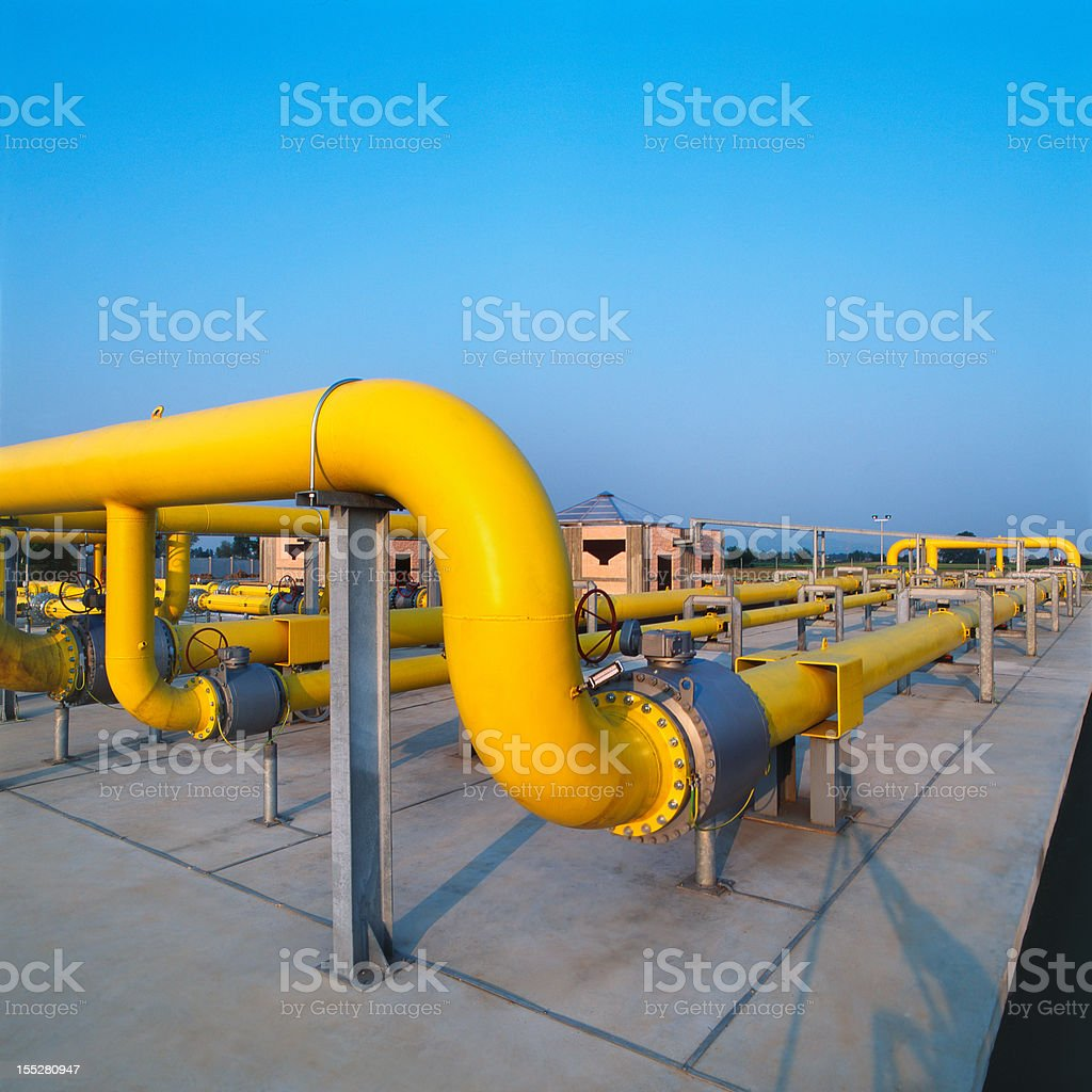 Yellow pipes in a gas distribution station, blue sky background royalty-free stock photo