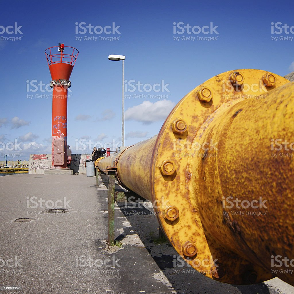 Yellow pipline and red lighthouse royalty-free stock photo