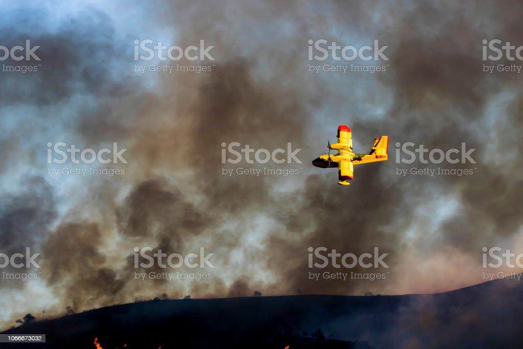 Yellow Plane Flies Through Smoky Sky in California Woolsey Brushfire stock photo