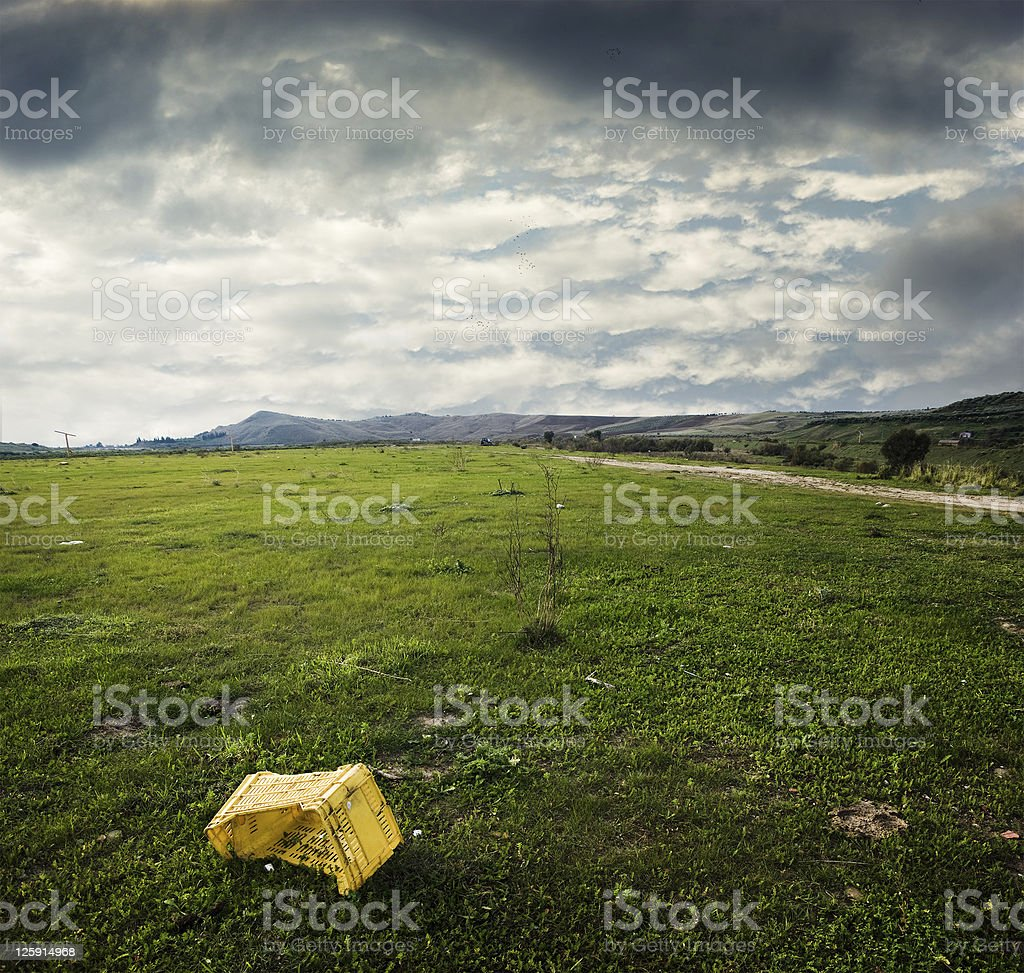 yellow plastic box abandoned in desolate grass area royalty-free stock photo
