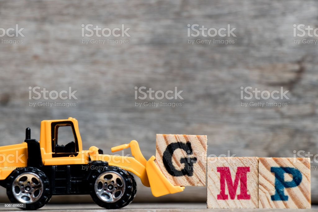 Yellow plastic bulldozer hold letter G to complete word GMP (Abbreviation of Good Manufacturing Practice) on wood background stock photo