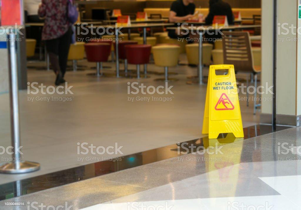 cone de plástico amarelo com sinal mostrando o aviso de chão molhado no restaurante, na loja de departamento - foto de acervo